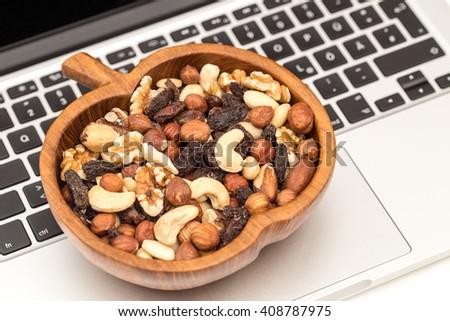Raw organic trail mix from cashew nuts, raisins, walnuts, macadamia,  hazelnuts, brazil nuts, almonds in apple wooden bowl on laptop keyboard background, close up - stock photo