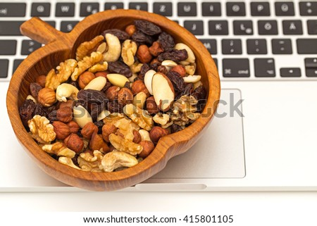 Raw organic trail mix from cashew nuts, raisins, walnuts, macadamia, hazelnuts, brazil nuts, almonds in apple olive wooden bowl on laptop keyboard background, close up - stock photo