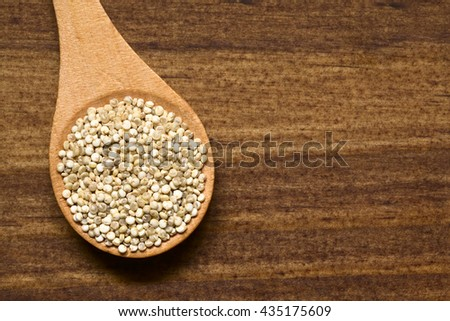 Raw organic white quinoa (lat. Chenopodium quinoa) grains on small wooden spoon, photographed overhead on dark wood with natural light