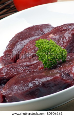 raw ostrich steak with parsley on a plate