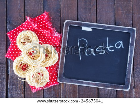 raw pasta and black board for menu and recipe - stock photo