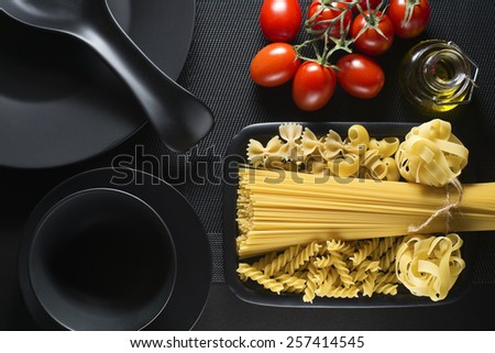 Raw pasta collection and tomatoes on black table - stock photo