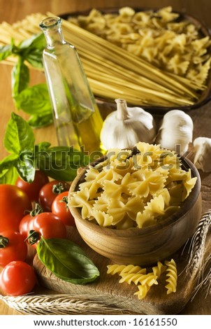raw pasta in a bowl with tomato, garlic and basil - stock photo