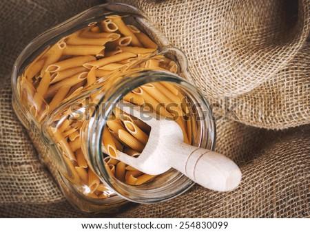 Raw pasta in a glass jar, haze effect - stock photo