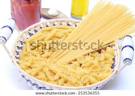 Raw pasta in basket - stock photo