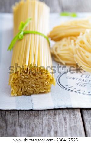 Raw pasta on a napkin Linguine and pasta nests - stock photo