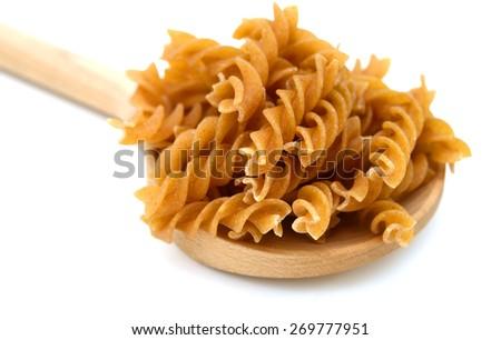 raw pasta on spoon on white background  - stock photo