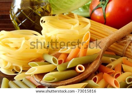 raw pasta on wood background - stock photo