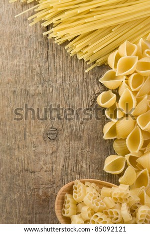 raw pasta on wood background texture - stock photo