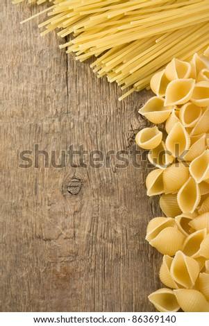 raw pasta on wood background texture - stock photo