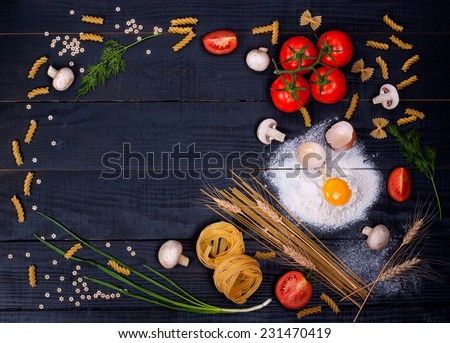 Raw pasta, tomatoes,mushrooms, flour and eggs on black wooden table background, top view and place for your text - stock photo
