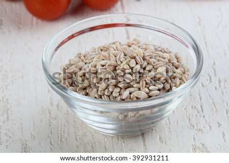 Raw pearl barley in the bowl on wood background