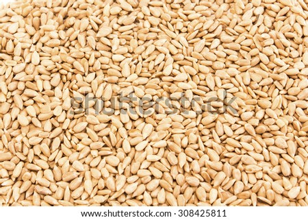 Raw, peeled sunflower seeds as background.