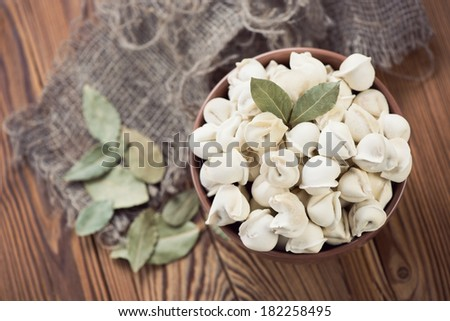 Raw pelmeni with bay leaves, view from above - stock photo