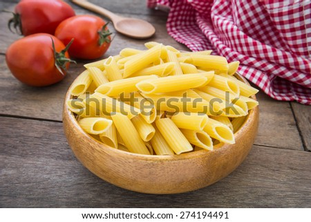 Raw penne pasta in wooden bowl - stock photo