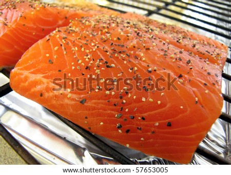 Raw peppered salmon prepped to cook on a grill sheet - stock photo