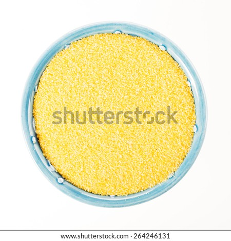 Raw polenta in blue bowl isolated on white background, viewed from directly above. - stock photo