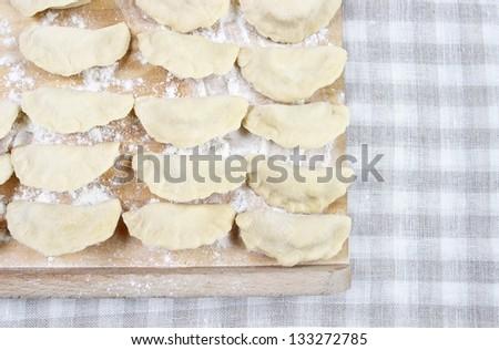 Raw polish dumplings lying on checked table cloth, copy space - stock photo