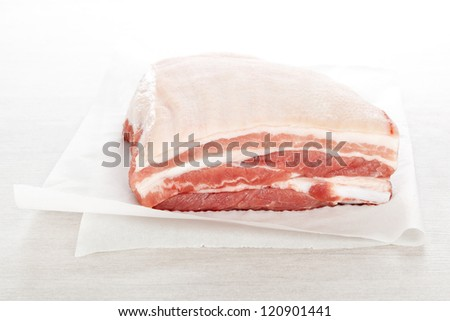 Raw pork belly portion on white baking paper on white background. Culinary meat eating.
