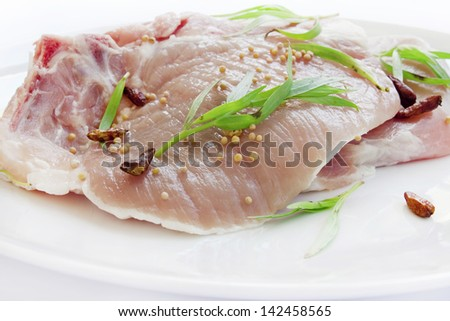 Raw pork chop fillets with spices
