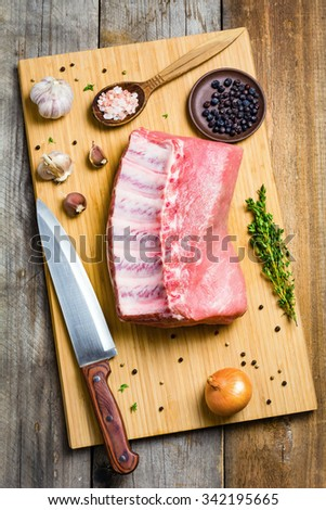 Raw pork chop on wooden cutting board with spices and chef knife, top view