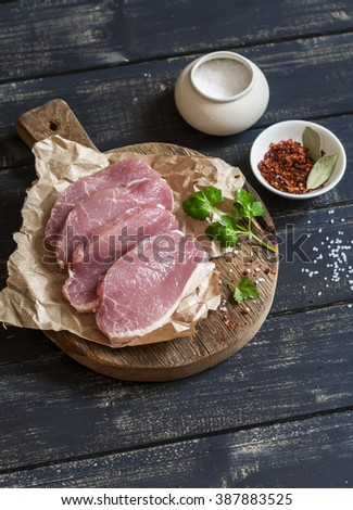 Raw pork chops and spices on a rustic wooden cutting board on a dark wooden background