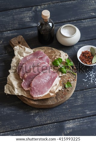 Raw pork chops and spices on a rustic wooden cutting board on a dark wooden background - stock photo
