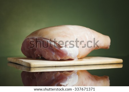 Raw pork leg on wooden cutting board ready for cooking - stock photo