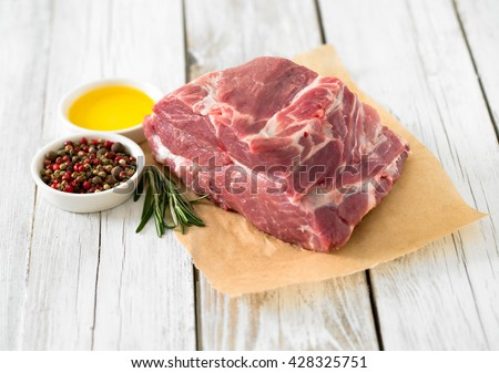 raw pork neck meat on wooden table - stock photo