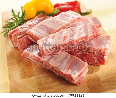 Raw pork ribs on a cutting board and vegetables - stock photo