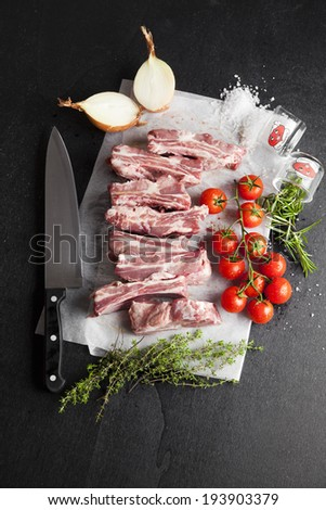 raw pork ribs with cherry tomato and herbs , onion , chef knife , thyme , salt , rosemary  - stock photo
