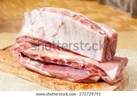 Raw pork spare ribs portion lying on wooden chopping board, uncooked culinary food ingredient ready to cut and prepare meal. Food product in horizontal orientation, nobody. - stock photo