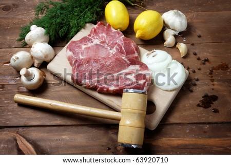 Raw pork steak and mallet on vintage table - stock photo