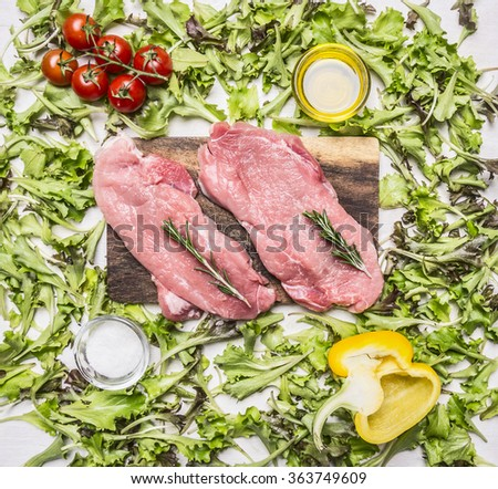 raw pork steak on vintage cutting board with lettuce, cherry tomatoes, bell pepper, oil and spices on wooden rustic background top view close up - stock photo