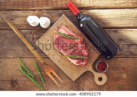 Raw pork steak with bottle of red wine, meat fork and rosemary on wooden background - stock photo