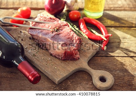 Raw pork steak with meat fork and bottle of red wine on wooden background - stock photo