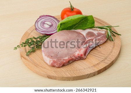 Raw pork steak with thyme and rosemary