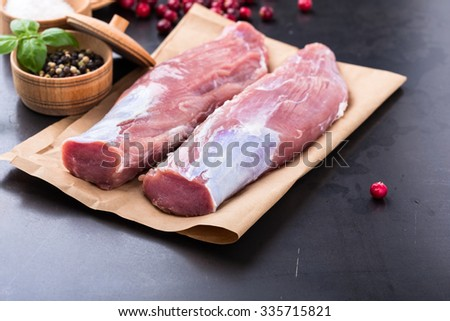 Raw pork tenderloin on craft paper ready to cook - stock photo