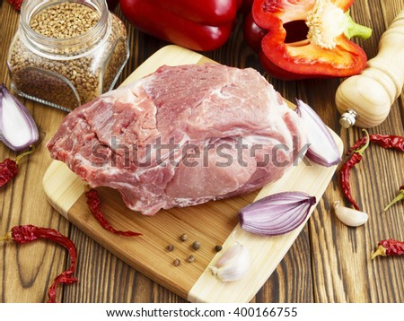 raw pork with vegetables and spices on wooden table - stock photo