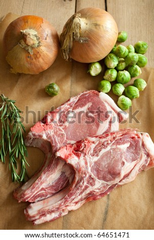Raw porkchops with onions and brussels sprouts