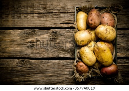 Raw potato food . Potatoes in an old box on a wooden table . Free space for text. Top view - stock photo