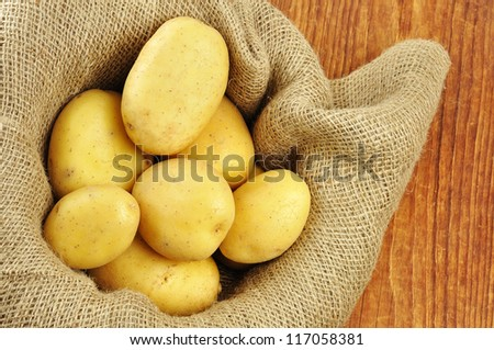 Raw potatoes in jute sack on a old wooden chopping board - stock photo