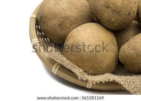 Raw potatoes in old basket with space for your text. - stock photo