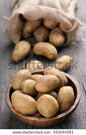 Raw potatoes on wooden table - stock photo