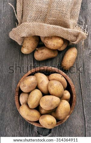 Raw potatoes on wooden table, top view - stock photo