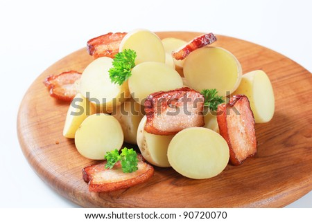 Raw potatoes with fried slices of pork belly