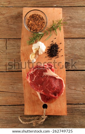 Raw prime rib beef steaks with spices, garlic and rosemary. - stock photo