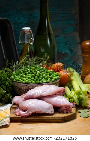 Raw rabbit foot, green peas, carrots, stalk celery, onion, bay leaves and olive oil for stew