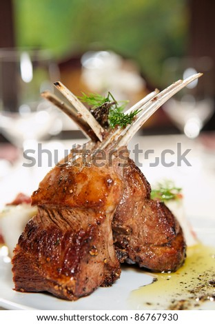 Raw rack of lamb fried with aromatic olive oil, herbs and spices - stock photo