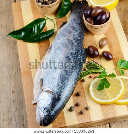 Raw rainbow trout on the chopping board with lemon and spices - stock photo